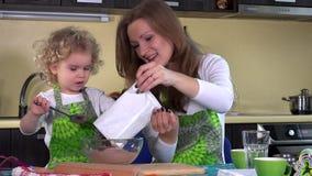 Kaukasische vrouw en haar weinig dochter het koken in keuken stock footage