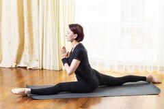 Kaukasische Vrouw het Praktizeren Yogaoefening binnen bij Heldere Middag Het zitten in Hanu Manasana stelt tijdens Eenzaamheidmed royalty-vrije stock fotografie