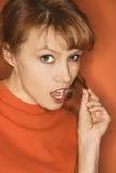 Kaukasische vrouw op oranje achtergrond. stock afbeeldingen