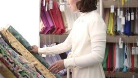 Kaukasische vrouw in wit in een weefselwinkel Overweegt de varianten van textiel Opent een broodje van stof met bloemen stock videobeelden