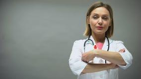 Kaukasische vrouwelijke arts met rood lint, internationaal HIV de voorlichtingsteken van AIDS stock video