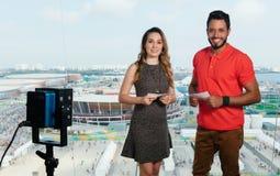 Kaukasische vrouwelijke presentator en Latijnse mens bij TV-studio royalty-vrije stock afbeeldingen