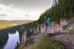 Kaukasische vrouwenwandelaar met rugzak die zich op een rots bevinden en aan het mooie landschap, Rusland, Ural kijken Stock Fotografie