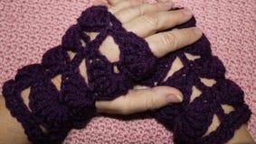 Kaukasische weibliche Hände, die purpurrote Häkelarbeit-Fingerless Handschuhe tragen Stockfotografie