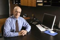 Kaukasische zakenman bij bureau. Stock Afbeelding