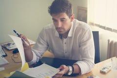 Kaukasische zakenman die bij zijn bureau werken stock afbeelding