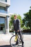 Kaukasische zakenman die een fiets berijdt stock foto