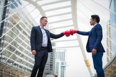 Kaukasische zakenman en Aziatische zakenman die met rode bokshandschoenen door stempel vechten Concept de bedrijfsconcurrentie royalty-vrije stock foto