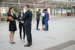Kaukasische zakenman en het Aziatische bedrijfsvrouw betekenen en het schudden hand het spreken over businessplan in de toekomst royalty-vrije stock afbeeldingen