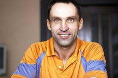 Kaukasische zitting thuis en glimlachend Stock Foto