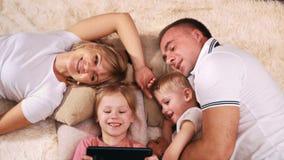 Kaukasischer Auftritt der jungen Familie auf Ihrem stillstehenden Lügen des freien Tages auf der Couch und dem Betrachten der Ta stock video footage