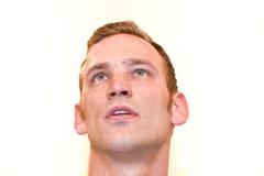 Kaukasischer blonder gutaussehender Mann, der oben, auf Weiß schaut Lizenzfreie Stockfotos