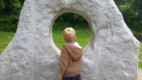 Kaukasischer blonder Junge, der durch Skulptur schaut Stockfoto