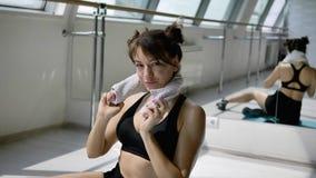 Kaukasischer Brunette in der schwarzen Sportkleidung kühlt weg mit weißem Tuch auf Boden ab stock footage