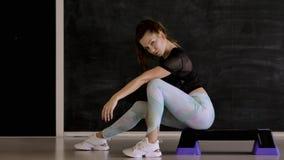 Kaukasischer Brunette in der Sportkleidung, die auf Kamera, schwarzer Hintergrund aufwirft stock video footage