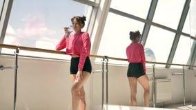 Kaukasischer Brunette in Trinkwasser der rosa Sportkleidung von der Flasche im Reinraum stock footage