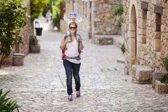 Kaukasischer Frauentourist, der ihren kleinen Sohn trägt lizenzfreie stockfotografie