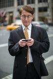 Kaukasischer Geschäftsmann, der auf Mobiltelefon simst Lizenzfreies Stockfoto