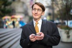 Kaukasischer Geschäftsmann, der auf Mobiltelefon simst Stockbilder