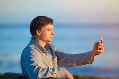 Kaukasischer Geschäftsmann, der Unterlassungsozean des Mobiltelefons an der Sonne hält Stockfotos