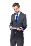 Kaukasischer Geschäftsmann gelesen auf Klemmbrett stockbild