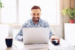 Kaukasischer glücklicher lächelnder Geschäftsmann, der an Laptop in seinem Büro arbeitet lizenzfreies stockfoto