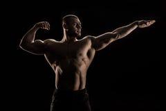 Kaukasischer hemdloser Athlet, der Muskeln biegt und weg schaut Lizenzfreie Stockbilder