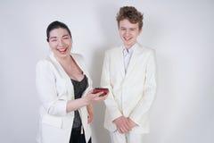Kaukasischer Jugendlicher in einem wei?en Anzug steht nahe bei freundlicher erwachsener asiatischer Frau und h?lt ein Telefon auf lizenzfreies stockbild