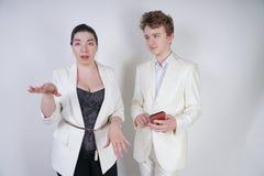 Kaukasischer Jugendlicher in einem wei?en Anzug steht nahe bei freundlicher erwachsener asiatischer Frau und h?lt ein Telefon auf lizenzfreies stockfoto