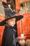 Kaukasischer Junge im farytale Karnevals-Zaubererkostüm, das Kerze hält lizenzfreies stockbild