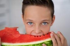 Kaukasischer Junge mit den ausdrucksvollen Augen, einen Biss einer saftigen Wassermelone nehmend Lizenzfreies Stockbild