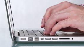 Kaukasischer junger Mann, der auf seinem Laptop schreibt stock video