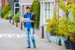 Kaukasischer junger Mann mit einem Stadtplan in den europäischen Ferien Lizenzfreies Stockbild