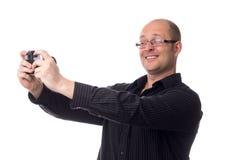 Kaukasischer Kerl macht ein Foto von unter Verwendung einer alten Kamera, die auf Weiß lokalisiert wird Stockbild