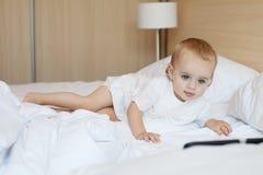 Kaukasischer kleines Mädchen aufpassender Film, unter Verwendung des Laptops im Schlafzimmer Stockfotos