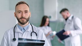 Kaukasischer männlicher Doktor mit Bart und Stethoskop im weißen Laborkittel, der Röntgenstrahlschnappschuß hält stock footage