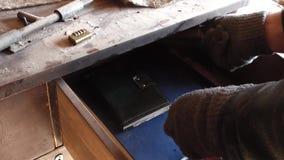 Kaukasischer Mann in den Handschuhen, die Fach in der alten Tabelle öffnen und etwas suchen stock footage