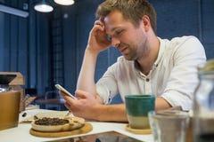 Kaukasischer Mann, der allein im Café sitzt und seine Freunde wartet Stockbilder