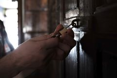 Kaukasischer Mann, der alte Holztür öffnet Lizenzfreies Stockbild