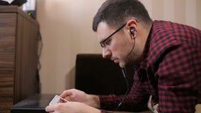 Kaukasischer Mann, der digitale Tablette auf Sofa verwendet und Musik hört stock video footage