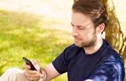 Kaukasischer Mann, der an einem Handy im Freien schaut Lizenzfreie Stockfotografie