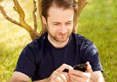 Kaukasischer Mann, der an einem Handy im Freien schaut Stockfotografie