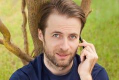 Kaukasischer Mann, der an einem Handy im Freien spricht Stockbild