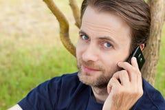 Kaukasischer Mann, der an einem Handy im Freien spricht Stockbilder