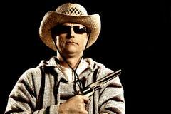 Kaukasischer Mann in der mexikanischen Kleidung, die Pistole anhält Stockfotografie