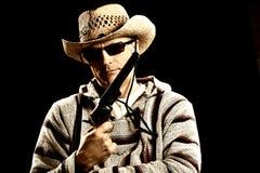 Kaukasischer Mann in der mexikanischen Kleidung, die Pistole anhält Lizenzfreies Stockfoto
