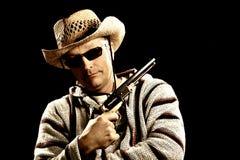 Kaukasischer Mann in der mexikanischen Kleidung, die Pistole anhält Lizenzfreie Stockfotografie