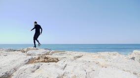 Kaukasischer Mann des jungen sportiven Sitzes im schwarzen Betrieb über den Felsen auf dem Strand Wellen, die an einem sonnigen w stock video footage