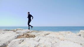 Kaukasischer Mann des jungen sportiven Sitzes im schwarzen Betrieb ?ber den Felsen auf dem Strand Wellen, die an einem sonnigen w stock video