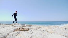 Kaukasischer Mann des jungen sportiven Sitzes im schwarzen Betrieb und im Springen über die Felsen auf dem Strand Wellen, die an  stock footage
